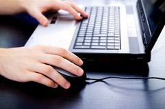 Male hands on notebook keyboard and mouse. Male hands on a notebook keyboard and mouse Stock Images