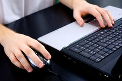 Male hands on notebook keyboard and mouse Stock Photography