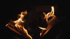 Male hands open the burning book. Male hands open a burning book in the dark in slow motion. Reverse video stock video