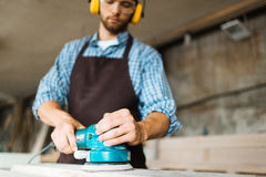 Male hands operating electric sander stock photo