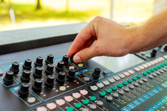 Male Hands operating small Sound console. On the table Stock Image