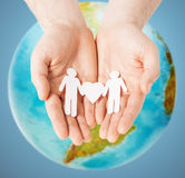 Male hands with paper gay couple figures and globe. Homosexuality, people, love and tolerance concept - close up of male hands holding gay couple paper man with Stock Photo