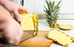 Male hands peeling fresh pineapple skin. Close up Royalty Free Stock Photos