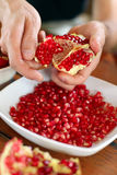Male hands peeling pomegranate fruit Royalty Free Stock Photography