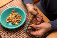 Male hands peeling walnuts Stock Photos