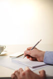 The male hands with a pencil and the cup Stock Photo