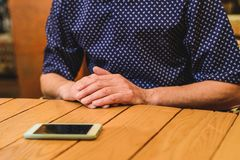 Male hands and phone are on the table. Horizontal frame royalty free stock photos