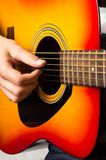 Male hands playing acoustic guitar, close up Royalty Free Stock Photos