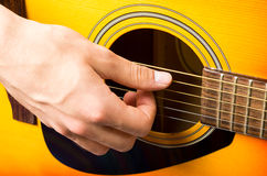 Male hands playing acoustic guitar, close up. Male hands playing acoustic orange and yellow guitar, close up Stock Images