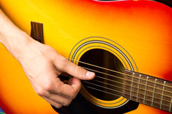 Male hands playing acoustic guitar, close up. Male hands playing acoustic orange and yellow guitar, close up Royalty Free Stock Photos