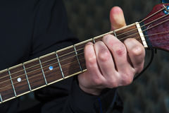 Male hands playing on acoustic guitar, closeup. Royalty Free Stock Photos