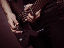 Male hands playing electric guitar. Male hands with electric guitar. Close up, part body adult person is holding instrument and playing. Hobby, music concept stock image