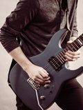 Male hands playing electric guitar. Male hands with electric guitar. Close up, part body adult person is holding instrument and playing. Hobby, music concept stock photography