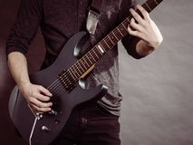 Male hands playing electric guitar. Male hands with electric guitar. Close up, part body adult person is holding instrument and playing. Hobby, music concept stock images