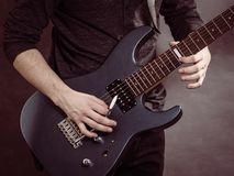 Male hands playing electric guitar. Male hands with electric guitar. Close up, part body adult person is holding instrument and playing. Hobby, music concept royalty free stock photo