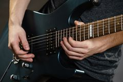 Male hands playing electric guitar. Male hands with electric guitar. Close up, part body adult person is holding instrument and playing. Hobby, music concept stock photo