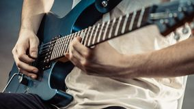 Male hands playing electric guitar. Male hands with electric guitar. Close up, part body adult person is holding instrument and playing. Hobby, music concept royalty free stock photography