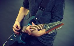 Male hands playing electric guitar. Male hands with electric guitar. Close up, part body adult person is holding instrument and playing. Hobby, music concept royalty free stock image