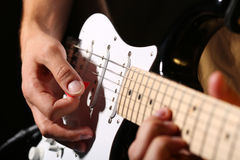 Male hands playing electric guitar with plectrum closeup Stock Photography