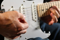Male hands playing electric guitar with plectrum closeup Stock Photos