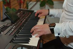 Male hands playing electric piano. Close up of the hand of a professional musician male piano player in suit playing an electric piano at a special event Royalty Free Stock Photos