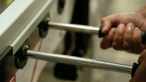 Male hands playing foosball game, enjoying fun and leisure with friends in pub. Stock footage stock footage