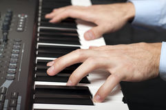 Male hands playing the piano. Closeup shot of male hands playing the piano in the studio Stock Images