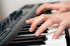 Male hands playing the piano. Closeup shot of male hands playing the piano in the studio Royalty Free Stock Photos