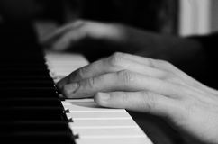 Male hands playing the piano. Black and white photo Royalty Free Stock Image