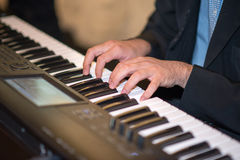Male hands playing the piano Stock Photos