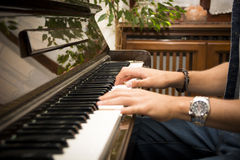 Male hands playing piano indoors Stock Images