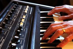 Male hands playing a vintage analogue synth in shallow focus.  stock photo