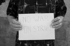 Male hands the poster with an inscription: no war on Syria. Male hands hold the poster with an inscription : no war on Syria stock photos