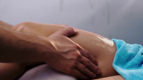 Male hands pouring oil and massaging patient's leg