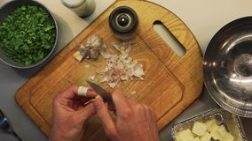 Male hands preparing food on a wooden cooking board top view