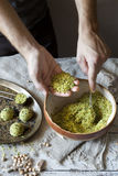 Male hands preparing homemade falafel with chickpeas flour on rustic table Stock Photo