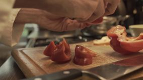 Male hands preparing paprika on a wooden cooking board. HD stock video footage