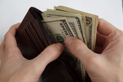 Male hands pulling a pile of American bank notes USD currency, US Dollars from a leather wallet Royalty Free Stock Photo