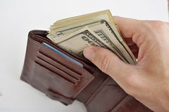 Male hands pulling a pile of American bank notes USD currency, US Dollars from a leather wallet as a symbol of successful person Stock Photo