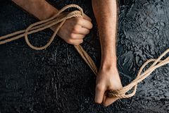 Male hands are pulling the rope on a black background. Symbolism containment of man`s connection by means of bound hands with a rope stock image