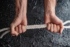 Male hands are pulling the rope on a black background. Symbolism of man`s connection by means of bound hands with a rope royalty free stock images