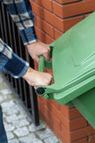 Male hands pushing a wheeled dumpster Royalty Free Stock Images