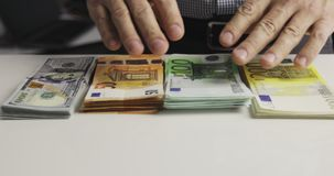 Male hands put bundles of money on the table. Denominations: two hundred euros, one hundred euros, fifty euros, one hundred dollars stock footage