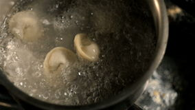 Male Hands Put Dumplings Into Boiling Water. Ravioli Cooking stock video