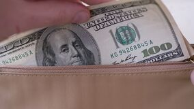 Male Hands Put Money in Hundreds Dollar Bills in Brown Leather Wallet. Close-up