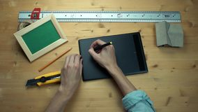 Male hands putting off sticky note with question sign using graphic tablet. At wooden desk. Metal ruler, house model, craft rope, realistic mockup wooden photo stock footage