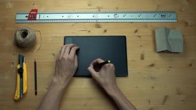 Male hands putting off sticky note with question sign using graphic tablet. Metal ruler, house model, craft rope, yellow paper knife at wooden desk stock video footage