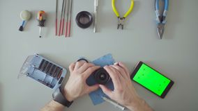 Male hands repair lens on grey table. Top view. Male hands scrolling a smartphone with green screen. Male hands repair photo lens on grey table stock footage