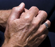 Male hands at rest. Strong male hands resting comfortably against dark background. Concept of contentment or comfort stock photos