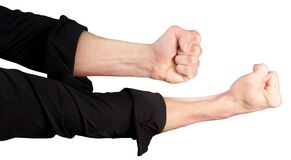 Male hands in rolled up sleeves of a black shirt with clenched fists
